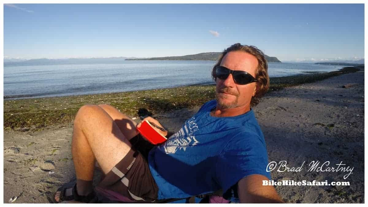 Updating the diary on the beach next to my campsite, Denman Island on my cycling vancouver island route
