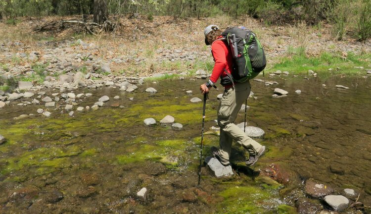 Crossing a river with hiking sticks